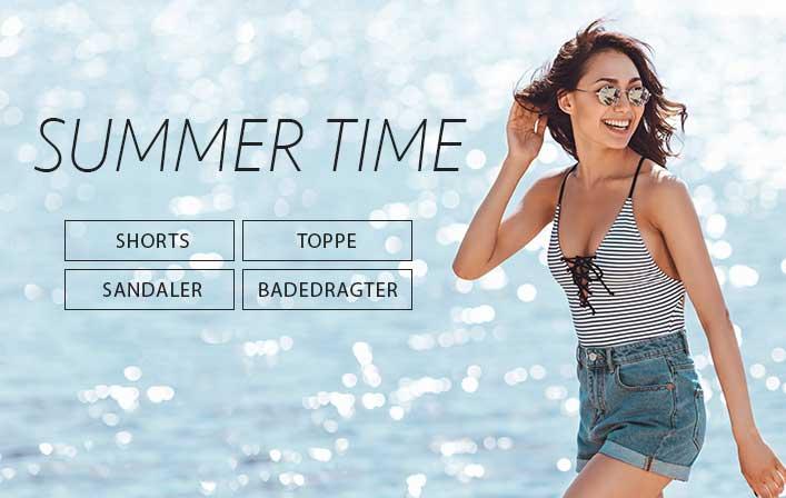 Pige med solbriller, badedragt og denim shorts på stranden